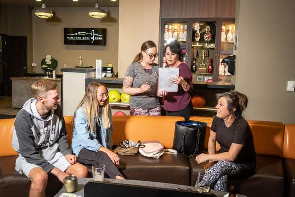 Family laughing and enjoying conversation while reviewing a menu