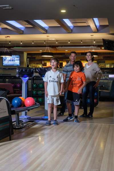 Family posing for a photo while playing a game of bowling