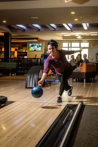 Woman throwing a bowling ball down a lane