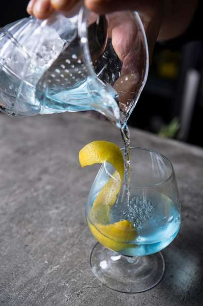 Server pouring water with lemon