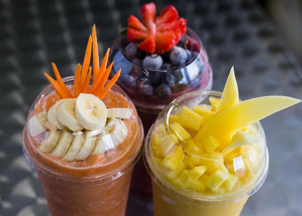three blended drinks topped with fruit