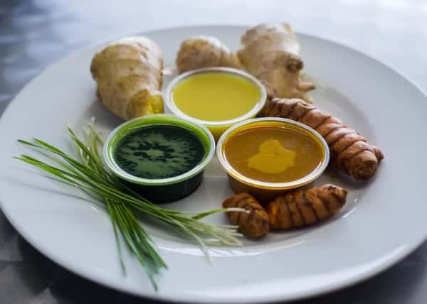 plate of wheatgrass and wheatgrass juice, ginger and ginger juice, and turmeric and turmeric juice