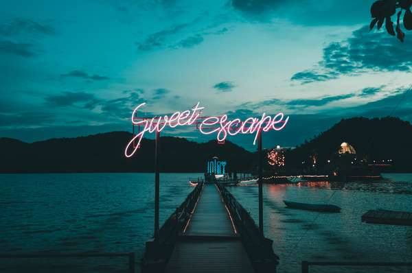 sweet escape neon sign on dock
