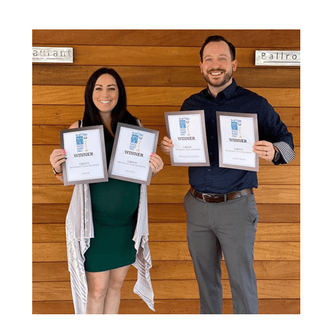 two people holding awards