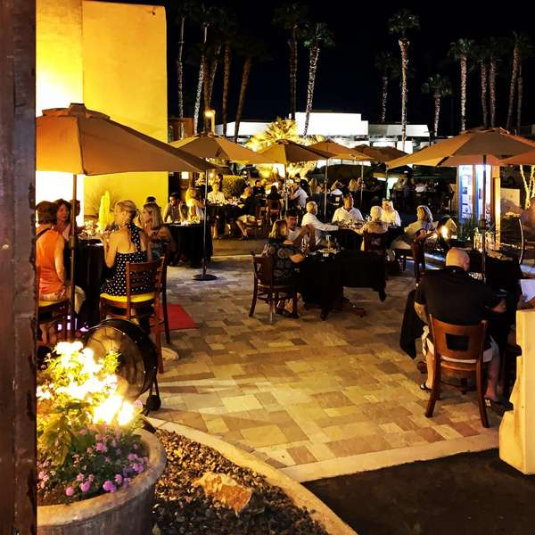 Outdoor dining tables with umbrellas front courtyard