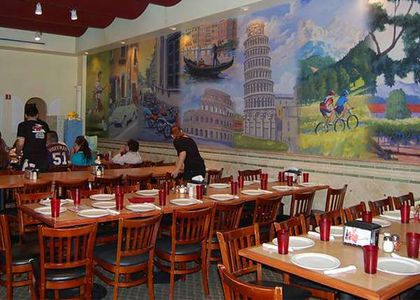 several tables set up for dinner with a mural