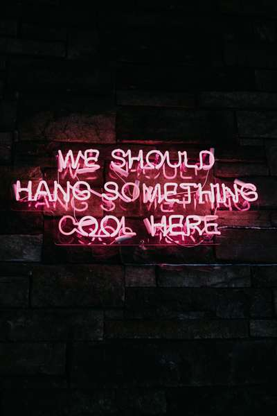 Neon pink sign that says We should hang something cool here
