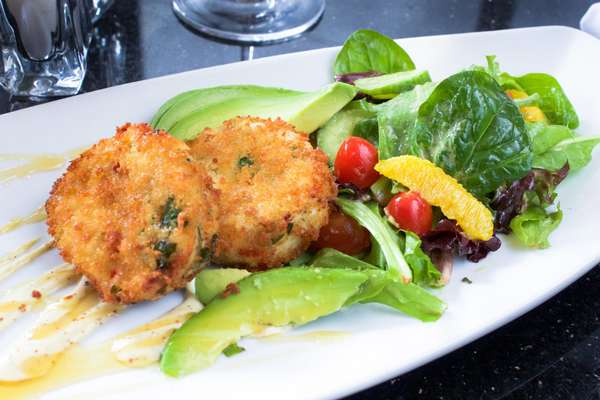 Blue Crab Cakes with crispy jumbo lump crab served with citrus avocado salad, cracked mustard seeds and micro greens.