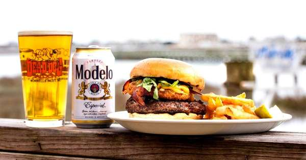 Burger with fries and a Modelo beer and a beer in a Dead Dogs Saloon glass