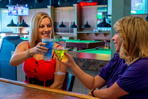 two women toasting at bar