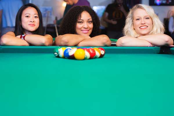 Three women leaning on pool table