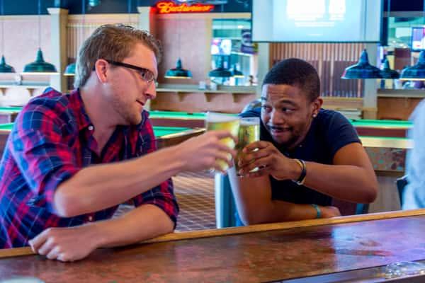 tow men toasting at bar