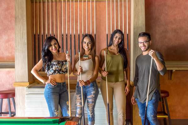 groups of people holding pool sticks