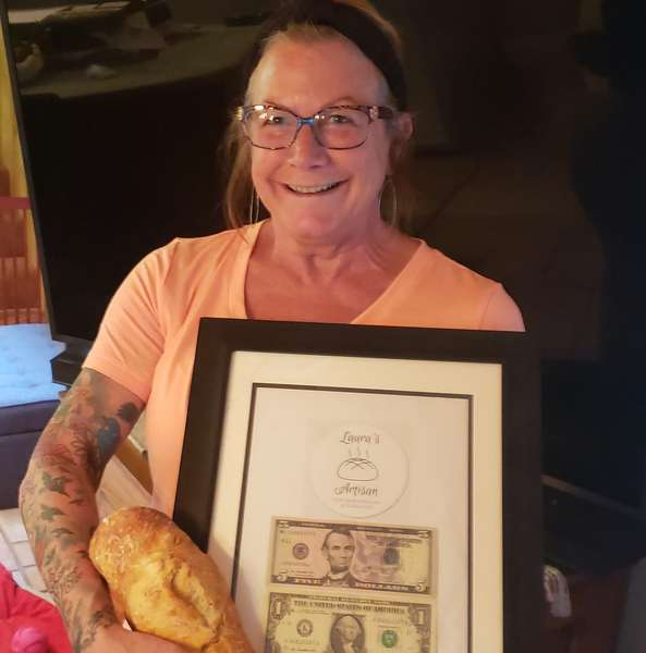 Laura holding money earned from her first bread sale