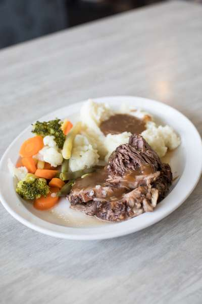 braised pot roast dinner with mashed potatoes, gravy, and vegetables