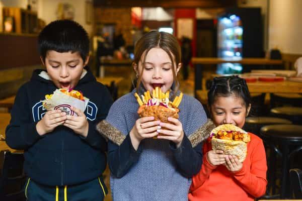 kids holding pita sandwiches