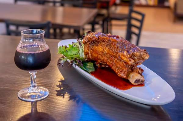 A photo of a wine glass and a delicious BBQ Rib.