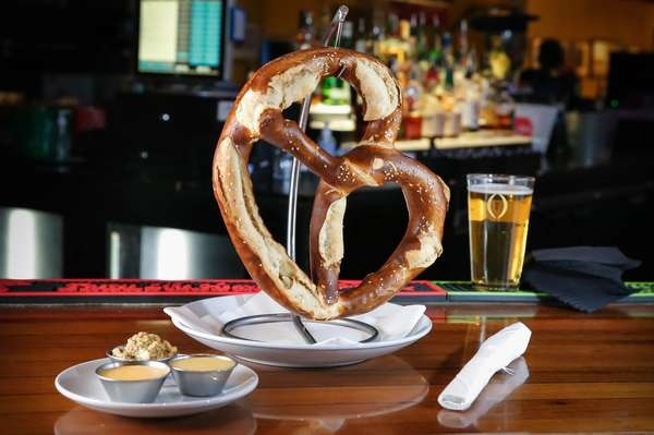 Large pretzel with various dipping sauces