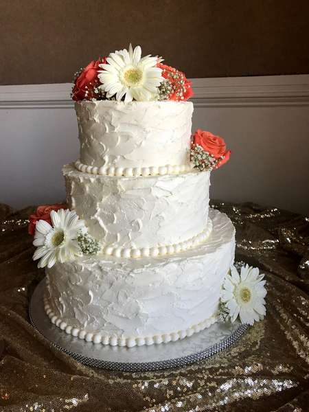 white cake with daisies