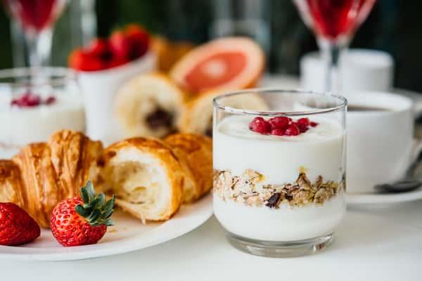 Yogurt parfaits with strawberries, granola, and pastries