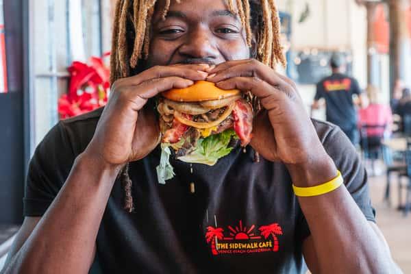 A Man Eating a John Irving Burger at The Sidewalk Cafe