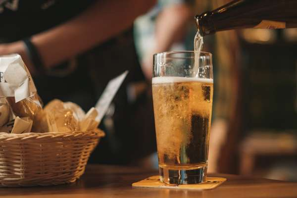 beer being poured and basket of food