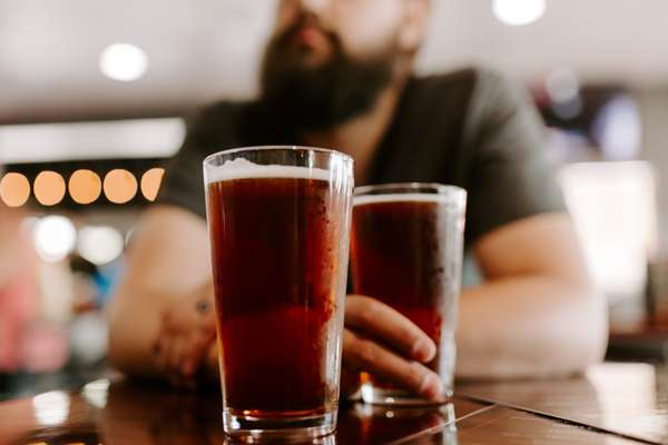 man sitting in front of two draft beers