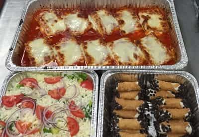 trays of lasagna, salad and cannolis