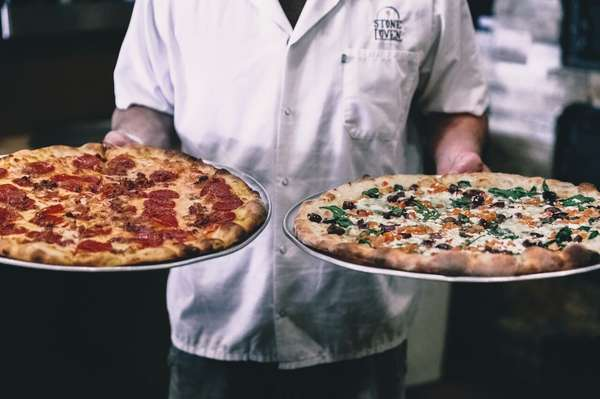 chef holding pizzas