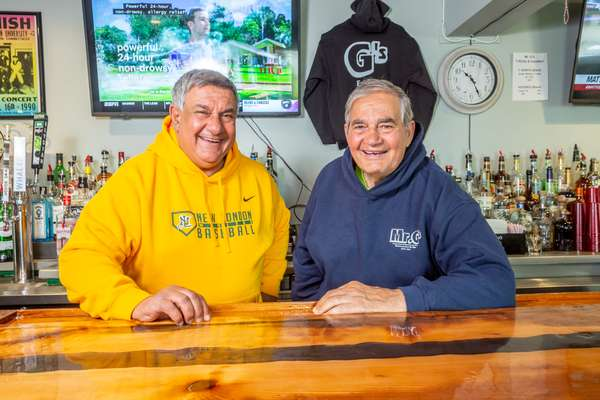 owners standing behind the bar