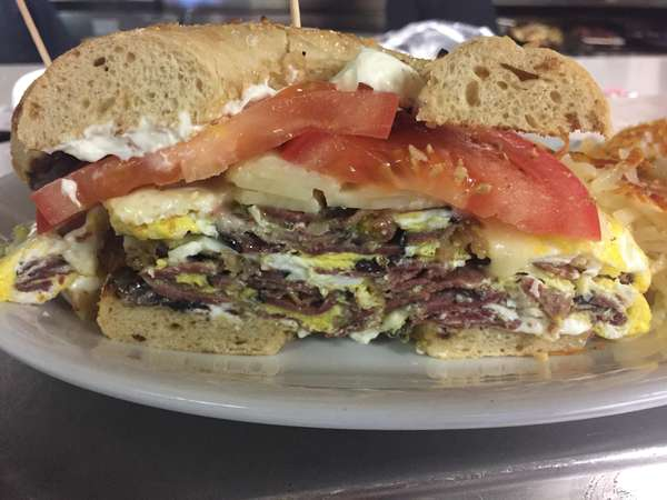 Pastrami and fried egg sandwich on a toasted bagel with melted Swiss cheese