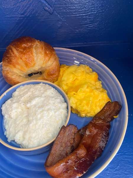 bacon grits eggs and croissant