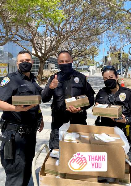 3 Santa Monica police, two men and one woman, standing outside with black masks each holding a box lunch in front of a cart full of Urth Caffé lunch boxes. Thank You is at bottom right.