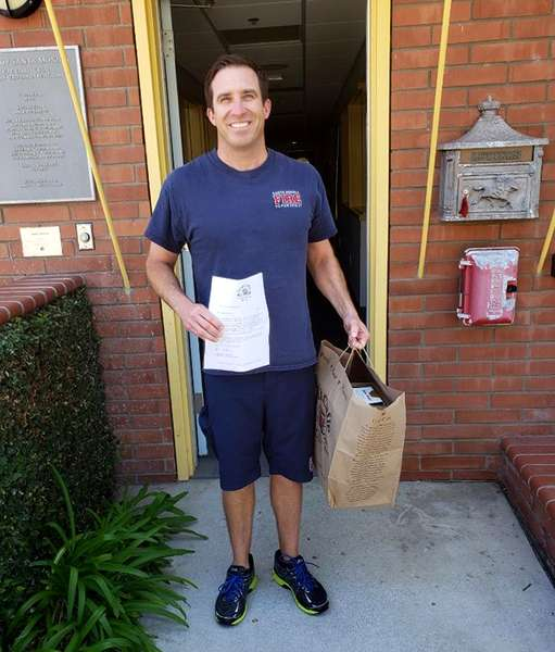 Santa Monica Fireman in blue T-shirt and shorts holding large Urth Caffé bag of lunch boxes. He is standing just outside a narrow doorway leading into the firestation.
