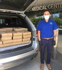 Back of mini-van packed with Urth Caffé lunch boxes with masked nurse getting ready to unload them.