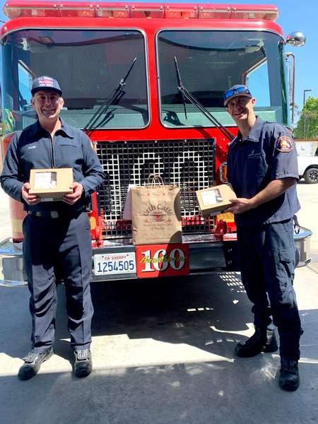 2 firemen holding Urth lunch boxes standing in front of red firetruck fr