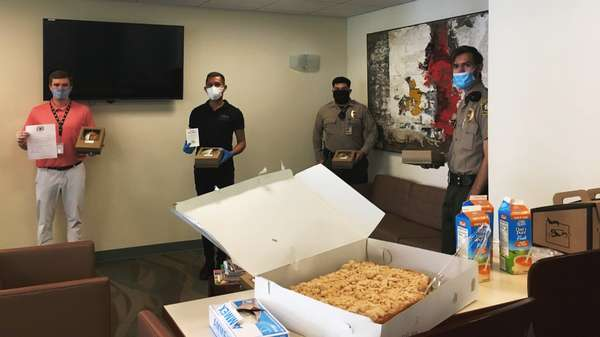 Room inside Beverly Hills City Hall with two officers and two staff member standing against walls. Table in foreground has large Urth Caffé crumb coffee cake, OJ cartons and paper coffee despensers.