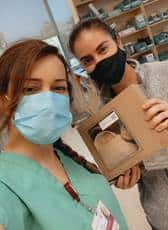 Two nurses upclose with masks, on is holding a lunch box from Urth Caffé.