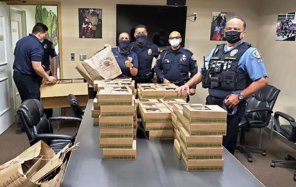 Five Pasadena police standing around conference table stated with Urth Lunch boxes.
