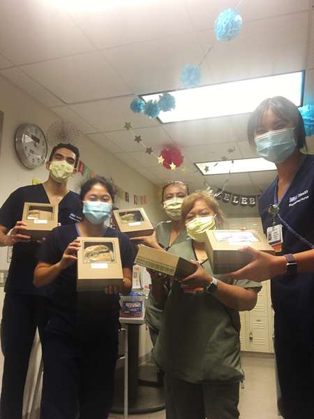 Group of five medical personel with masks in hallway all holding lunch boxes.