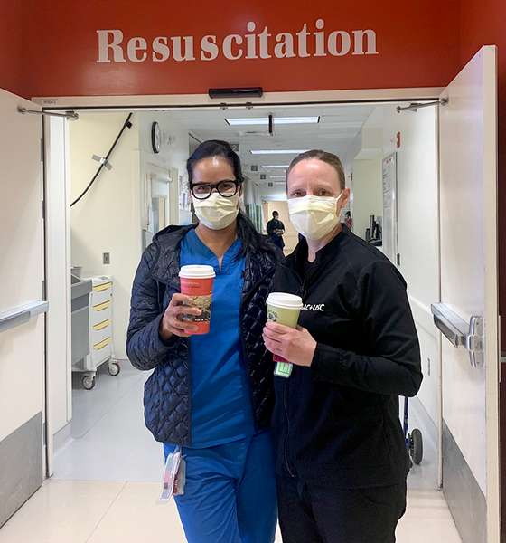 """Two nurses with medical masks holding Urth Caffé To Go coffee cups. They are standing in front of open double doors with """"Resuscitation"""" above them."""