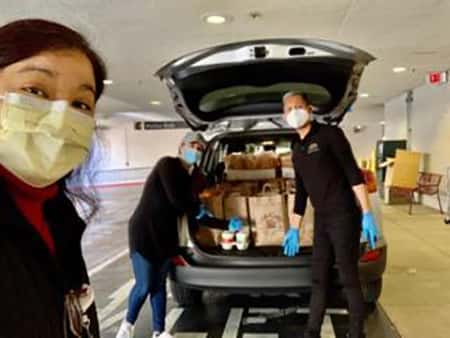 Three nurses unloading back of minivan full of Urth Caffé food bags and lunch boxes.