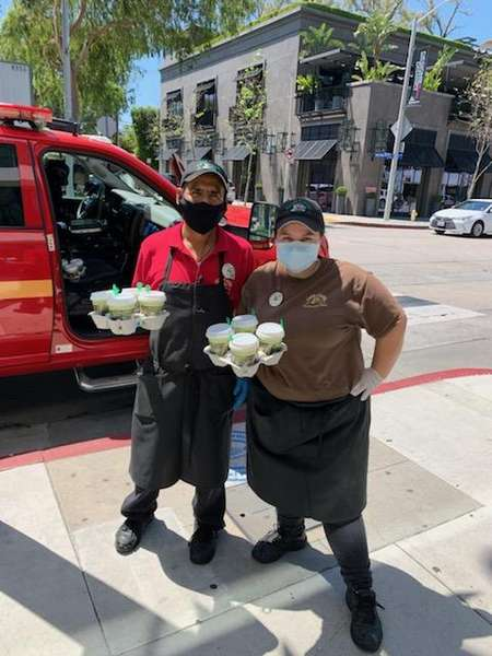 2 Urth Melrose employees holding drinks in from of parked emergency vehicle