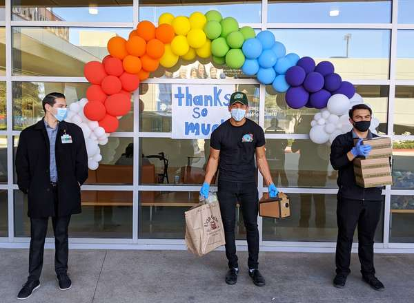 Three people standing in front of large glass window of St. Joseph's hospital with band of balloons and Urth Lunch boxes and bags.