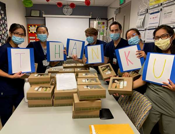Six nurses with masks standing around table full of Urth lunch boxes each holding a large card with a letter on it together spelling T H A N K U.