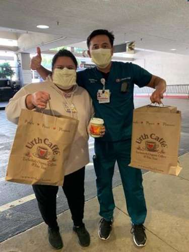 Male and female nurses with masks holding Urth food bags, coffee cup and giving thumbs up.