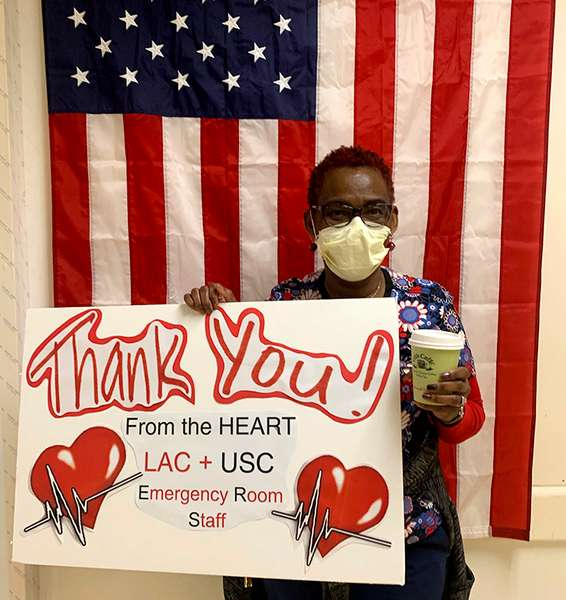 One USC nurse wearing yellow medical mask holding a sign with two big red hearts that reads: Thank You! From the HEART LAC + USC Emergency Room Staff. She is also holding a green Urth Caffé coffee cup and standing in front of a vertical USA flag.