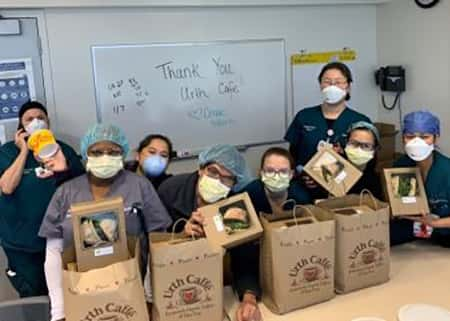 Group of nurses with masks in room with 4 Urth bags and 4 lunch boxes on table with dry erase white board behind them that say, Thank You Urth Caffé!