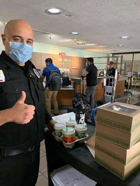 Security guard with mask standing next to cart of Urth lunch boxes and coffee cups giving thumbs up.