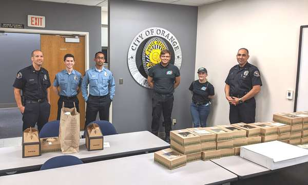Four City of Orange policemen with two Urth employees standing in front of City seal on wall and behind a table full of Urth lunch boxes and coffee